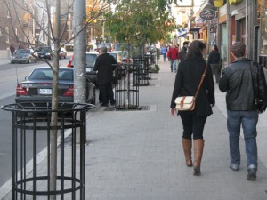 Two friends enjoy a walk up the tiled sidewalk on Roncesvalles Ave.