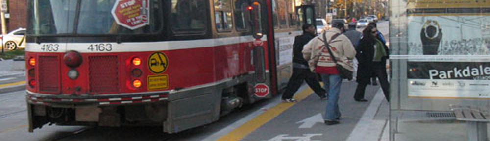 Streetcar unloads passengers onto bumpout on Roncesvalles Avenue.