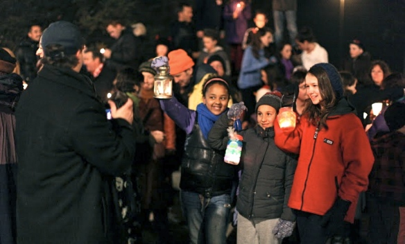 People from the Roncesvalles Village dressed in winter coats share the light of their candles at the end of their Earth Hour walk down Roncesvalles Avenue.