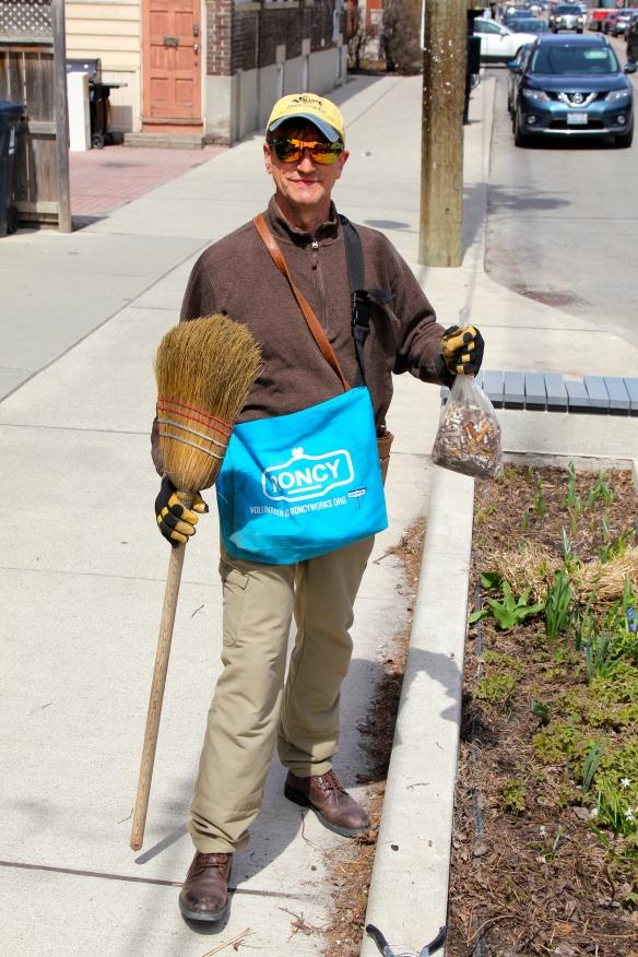 RoncyWorks volunteer holding broom and bag of cigarette litter.