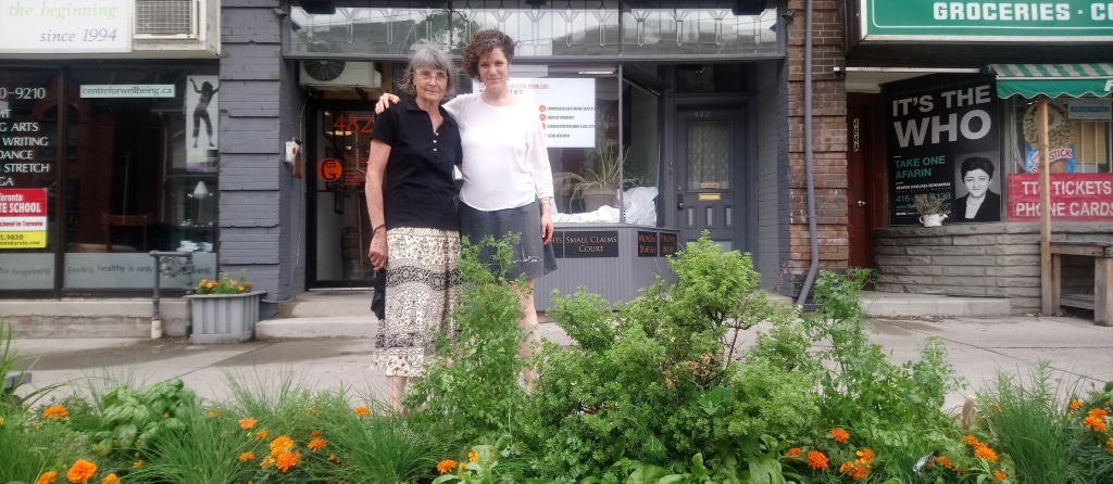 Volunteer Gardener and BIA Member stand behind the street garden they collaborated on.